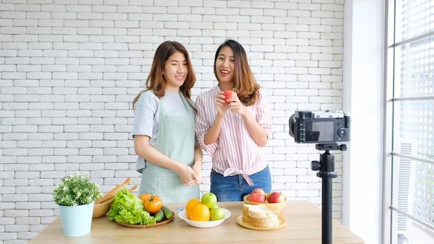 Twee jonge aziatische vrouwenvoedsel bloggers die terwijl het opnemen van video met gelukkig ogenblik spreken