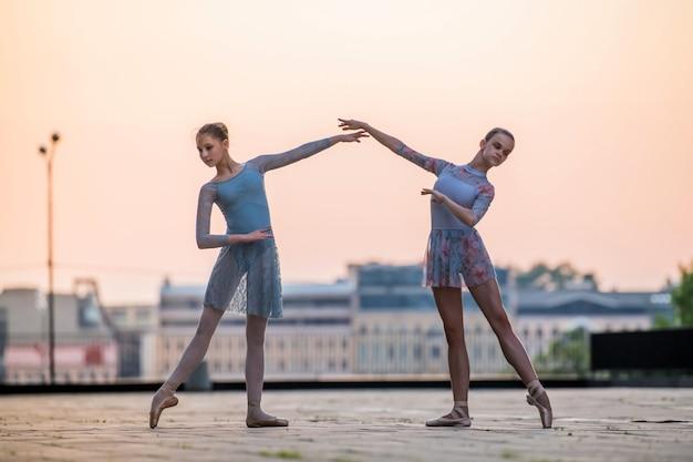 Twee jonge ballerina's dansen in pointe-schoenen in de stad tegen de achtergrond van de avondrood
