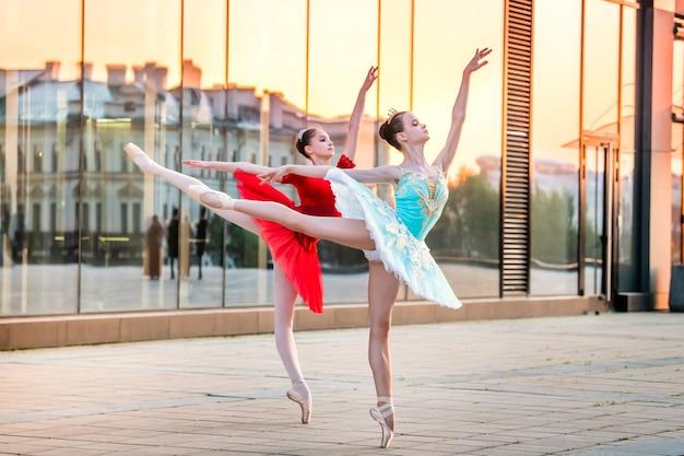 Twee jonge ballerina's in een felrode en blauwe tutu dansen tegen de achtergrond van de weerspiegeling van de stadszonsondergang