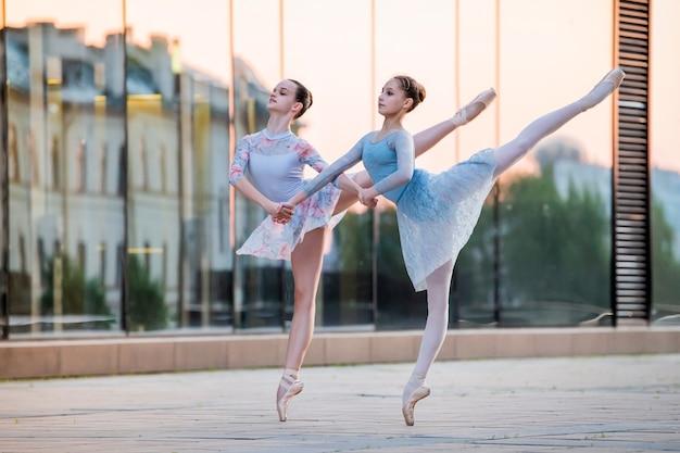 Twee jonge ballerina's in pointe-schoenen dansen tegen de achtergrond van de weerspiegeling van de stadszonsondergang in de spiegelmuur van het gebouw