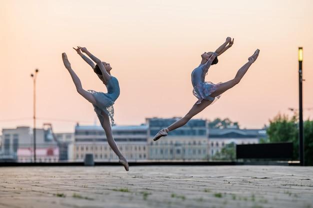 Twee jonge ballerina's vliegen in een sprong in pointe-schoenen in de stad tegen de achtergrond van de avondrood