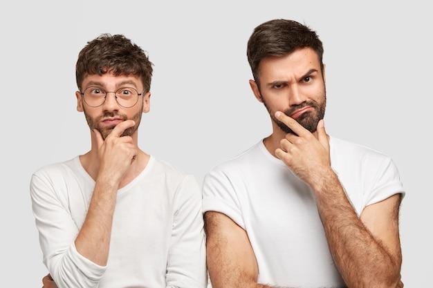 Twee jonge, bebaarde mannen houden hun kin vast en kijken serieus naar de camera, peinzen over het maken van een project