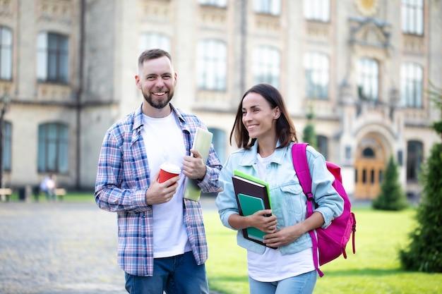 Twee jonge beste vrienden van de universiteit in vrijetijdskleding met rugzak hebben een gesprek op de campus en lachen