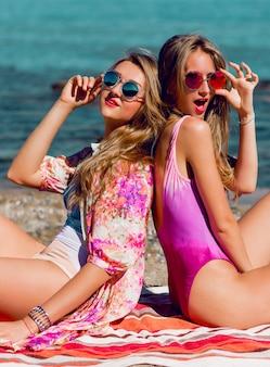 Twee jonge beste vrienden zittend op het tropische strand en genieten van de zomervakantie.
