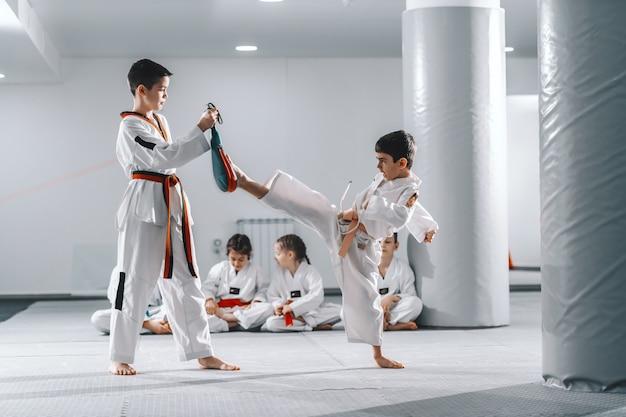 Twee jonge blanke jongens in doboks met taekwondo training op sportschool. een jongen schopt terwijl een andere een schopdoel vasthoudt.