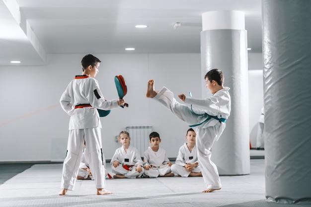 Twee jonge blanke jongens in doboks met taekwondo training op sportschool. een meisje schopt terwijl een ander een schopdoel vasthoudt