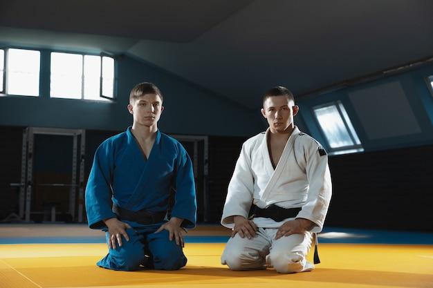 Twee jonge blanke judo-jagers in witte en blauwe kimono met zwarte gordels die zelfverzekerd in de sportschool poseren, sterk en gezond.
