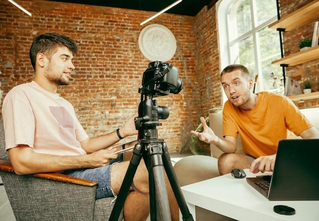 Twee jonge blanke mannelijke bloggers in vrijetijdskleding met professionele apparatuur of camera opname video-interview thuis. bloggen, videoblog, vloggen. praten tijdens live streamen binnenshuis.