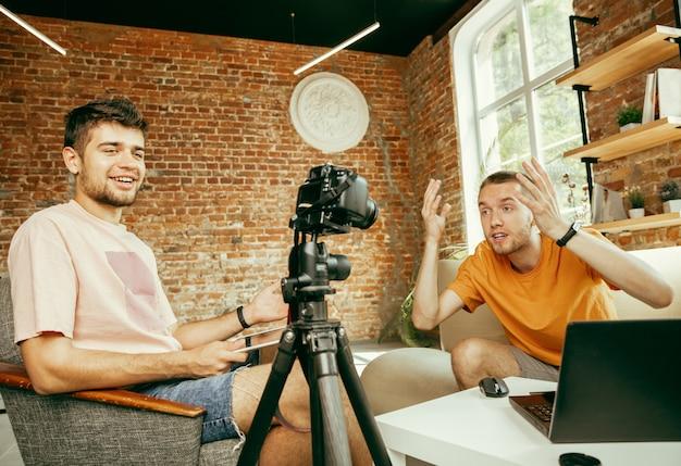 Twee jonge blanke mannelijke bloggers in vrijetijdskleding met professionele apparatuur of camera opname video-interview thuis