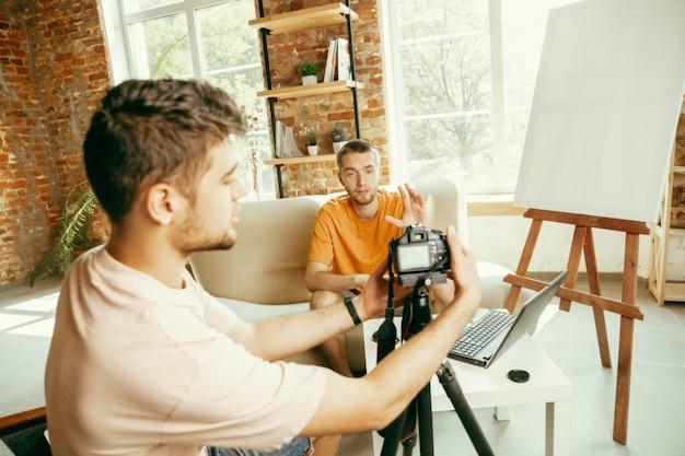 Twee jonge blanke mannelijke bloggers in vrijetijdskleding met professionele apparatuur