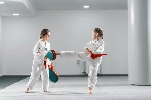 Twee jonge blanke meisjes in doboks met taekwondo training bij sportschool. een meisje schopt terwijl een ander een schopdoel vasthoudt.