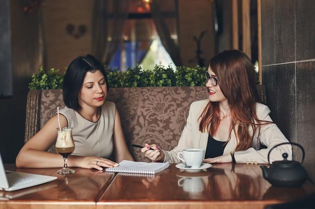 Twee jonge blanke ondernemers met laptop. vrouwen in café