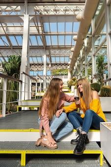 Twee jonge blanke vrouwen zitten graag in een stadskas omringd door planten en cactussen