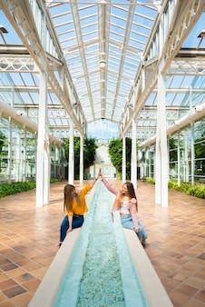 Twee jonge blanke vrouwen zitten graag op de rand van een fontein met water in een lichte kas
