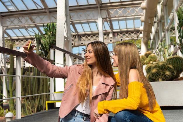 Twee jonge blonde blanke vrouwen genieten van de telefoon zittend op een trap in een stedelijke kas met de witte structuur omgeven door planten en cactussen