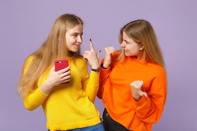 Twee jonge blonde tweelingzusjes meisjes in levendige kleding met de vingers omhoog, opzij met mobiele telefoon geïsoleerd op pastel violet blauwe muur. mensen familie levensstijl concept.