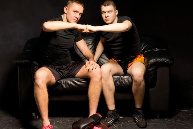 Twee jonge boksers geven elkaar een high five van felicitaties na een succesvolle trainingssessie