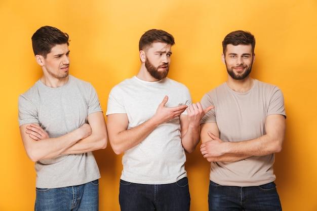 Twee jonge boos mannen kijken naar hun mannelijke vriend
