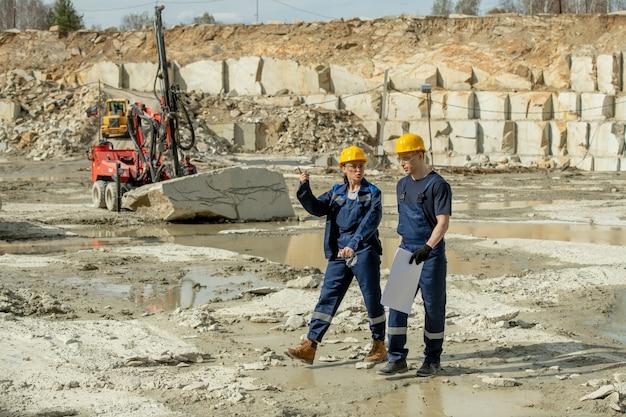 Twee jonge bouwers bespreken werkpunten terwijl ze door de bouwplaats lopen