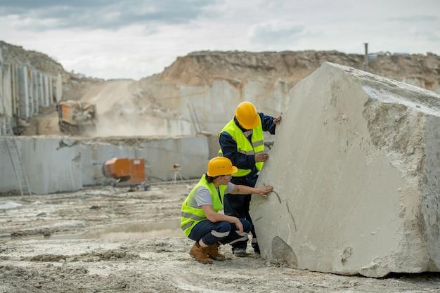 Twee jonge bouwers in veiligheidshelmen en uniform werken door een enorm stuk beton
