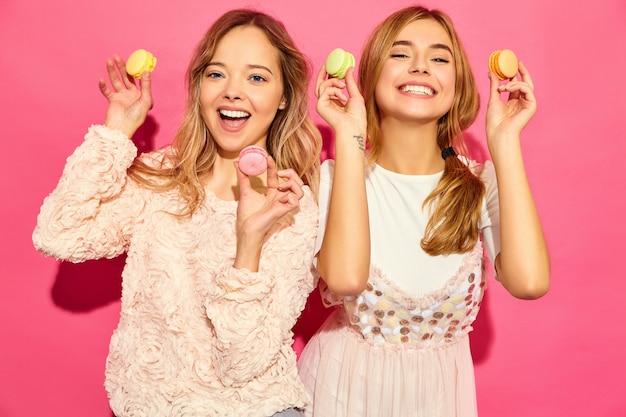 Twee jonge charmante mooie glimlachende hipster vrouwen in trendy zomerkleren. vrouwen met kleurrijke makarons, die macarons houden dichtbij gezicht. poseren op roze muur