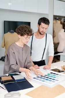 Twee jonge collega's bespreken kleurstalen per werkplek terwijl ze de juiste kiezen voor de modecollectie