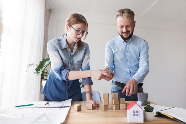 Twee jonge collega's die houten blok op bedrijfsbureau stapelen