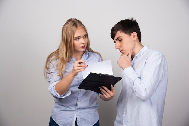 Twee jonge collega's op kantoor bespreken een project op grijze muur.