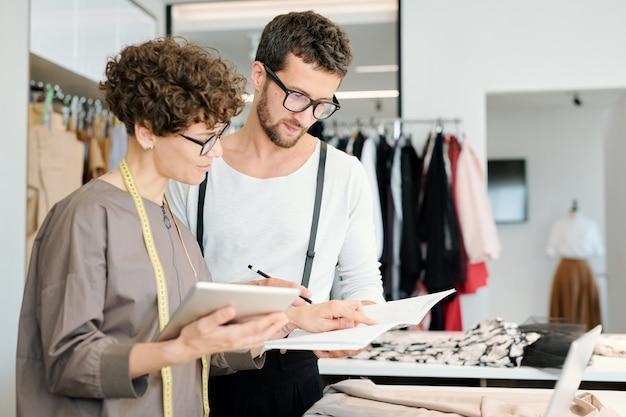Twee jonge creatieve modeontwerpers kijken naar nieuwe schets voor seizoenscollectie en bespreken deze