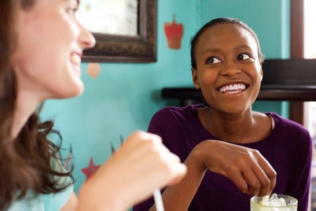 Twee jonge dames die in een koffie kletsen