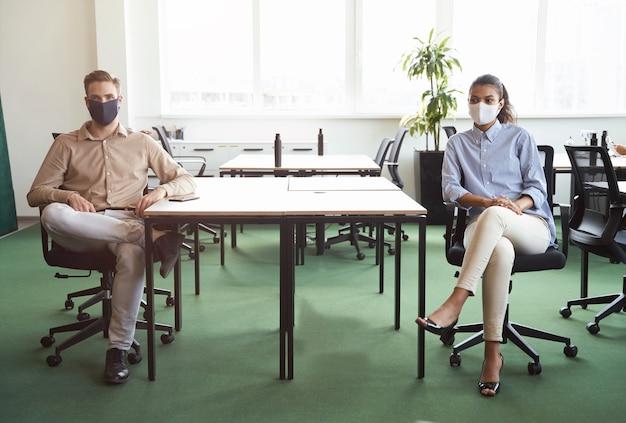 Twee jonge, diverse collega's die een beschermend gezichtsmasker dragen terwijl ze naar de camera kijken terwijl ze aan het bureau zitten