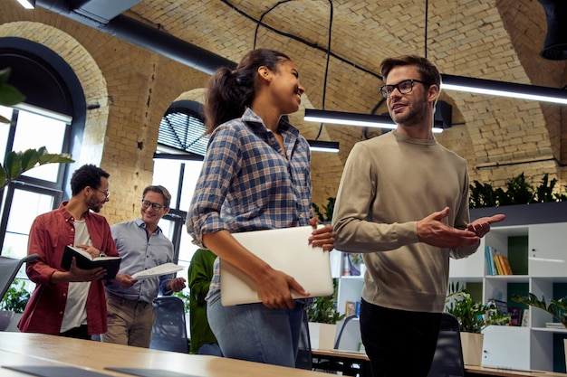 Twee jonge, diverse zakenmensen, mannelijke en vrouwelijke collega's die over iets praten terwijl ze binnenlopen