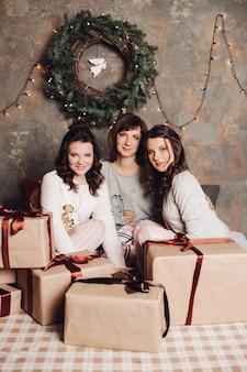 Twee jonge dochters met hun mooie volwassen moeder zitten in het midden van verpakte kerstcadeautjes tegen kerstkrans