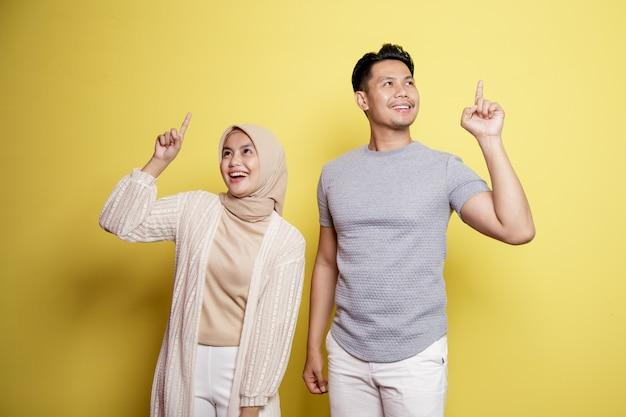 Twee jonge, een vrouw hijab en een man met een gelukkige uitdrukking hebben samen iets goeds geïsoleerd op gele achtergrond