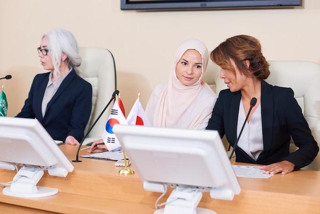 Twee jonge elegante interculturele vrouwen die op conferentie overleggen over rapporteerpunten van hun collega