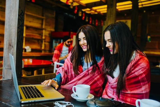 Twee jonge en mooie meisjes die aan tafel zitten en iets zoeken op internet