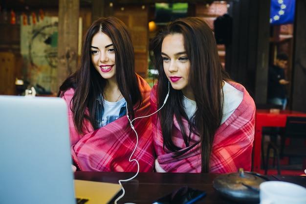 Twee jonge en mooie meisjes die aan tafel zitten en op zoek zijn naar iets op internet