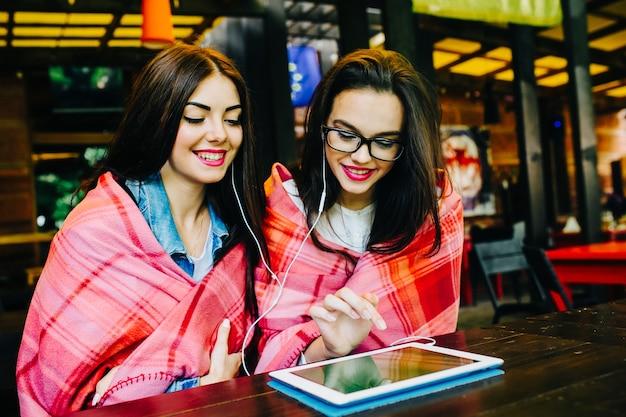 Twee jonge en mooie meisjes die aan tafel zitten te kijken naar iets op een tablet