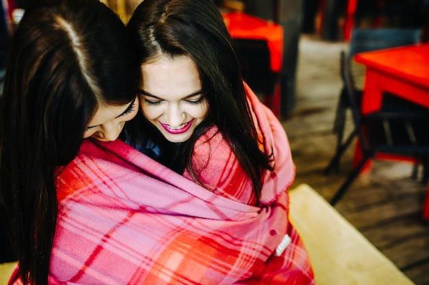 Twee jonge en mooie meisjes die elkaar vasthouden en plezier hebben in café