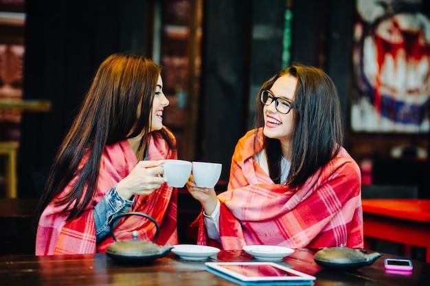 Twee jonge en mooie meisjes roddelen op het terras met een kopje koffie