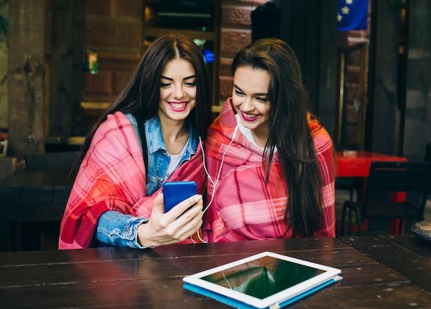 Twee jonge en mooie meisjes zitten aan de tafel en luisteren naar muziek met een smartphone