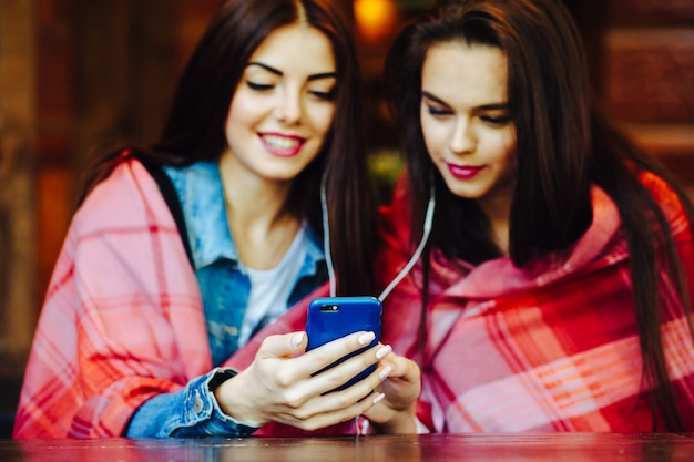 Twee jonge en mooie meisjes zitten aan tafel en luisteren naar muziek met een smartphone