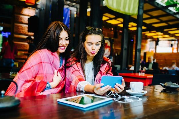 Twee jonge en mooie vrouwen zitten aan tafel en doen selfie in het café
