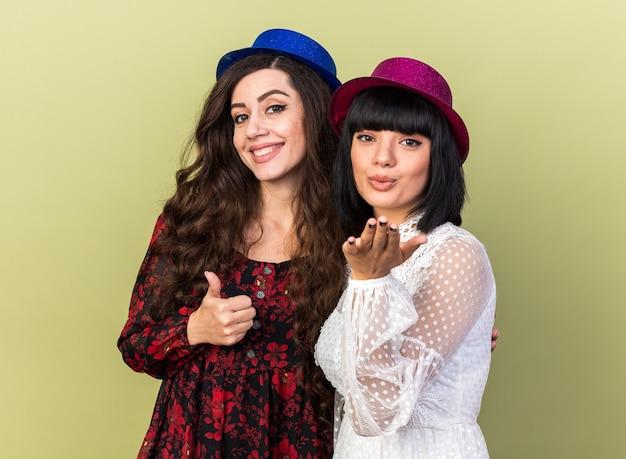 Twee jonge feestmeisjes met een feestmuts, beide met een duim omhoog geïsoleerd op een olijfgroene muur