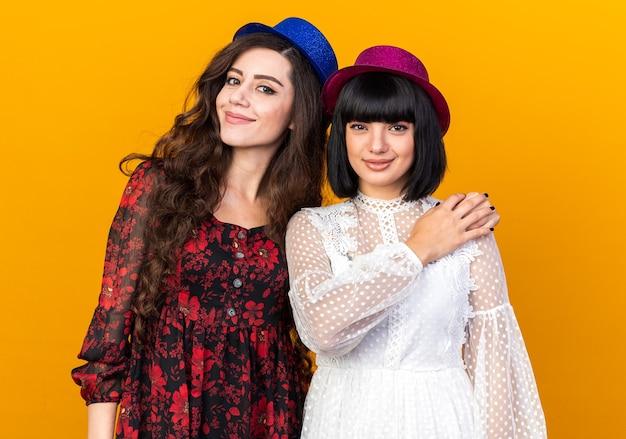Twee jonge feestvrouwen met een feestmuts die allebei naar de voorkant kijken geïsoleerd op een oranje muur