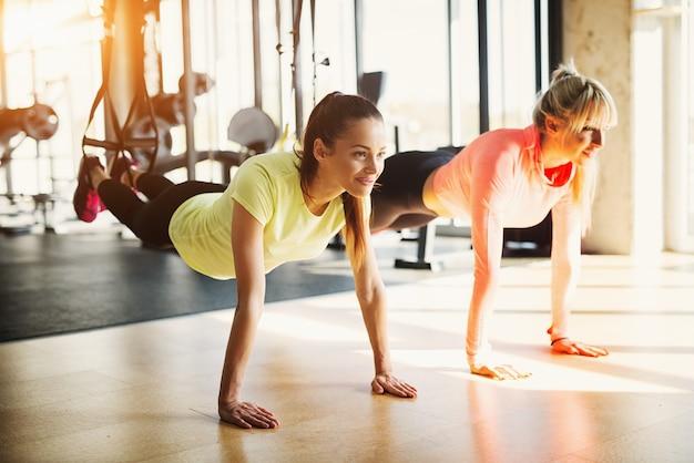 Twee jonge fit meisjes in een sportschool doen trx schorsing training.
