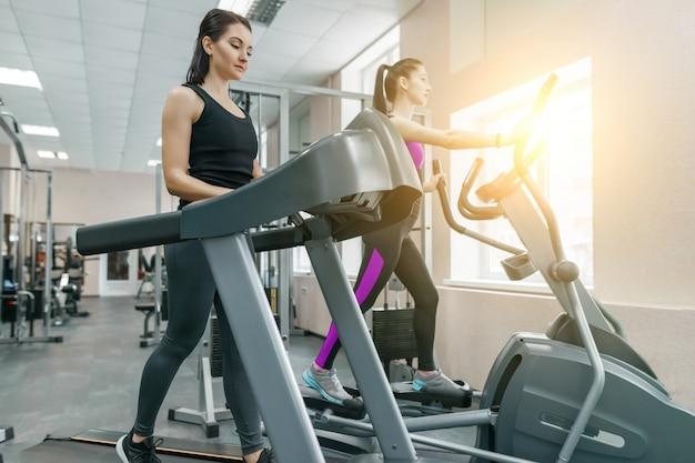 Twee jonge fitness gezonde vrouwen op de loopband in de sport moderne sportschool