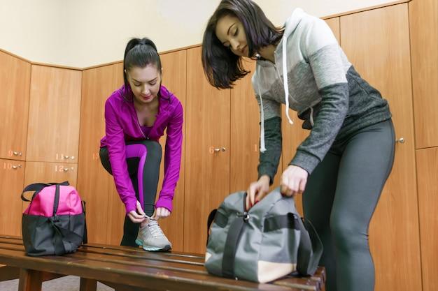 Twee jonge fitness vrouwen in kleedkamer in de sportschool