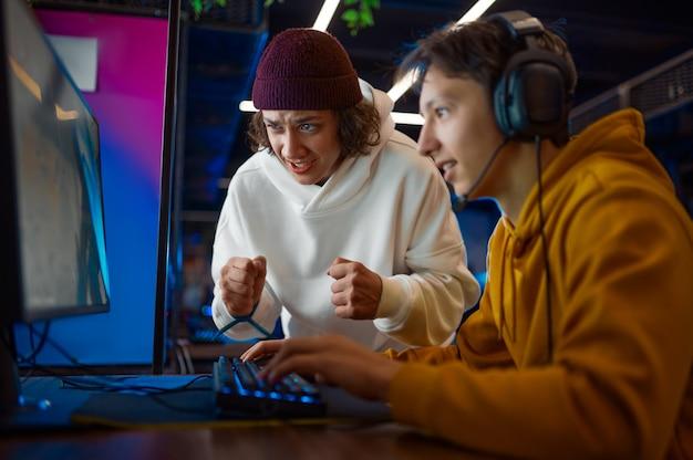 Twee jonge gamers kijken op de monitor in gamingclub