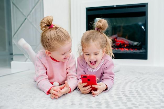 Twee jonge gefocuste kinderen spelen een smartphone zonder naam op de vloer van de woonkamer. jonge kinderen en techniek, zussen spelen met een mobiele telefoon, bekijken video's of spelen spelletjes